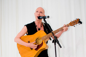 Richard O'Brian playing guitar