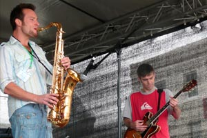two men playing saxophone and electric guitar on stage